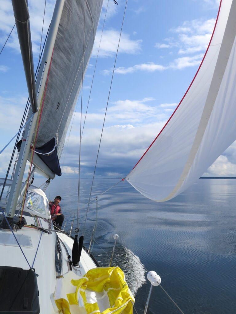 Spegelblankt hav men segling med spinnaker.