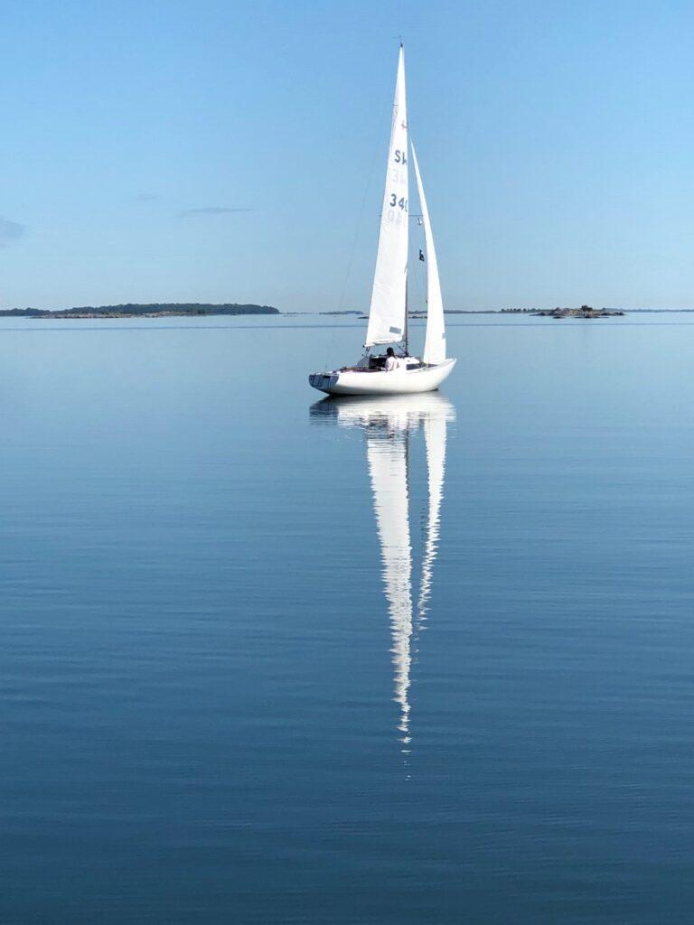 En Segelbåt på spegelblankt vatten.