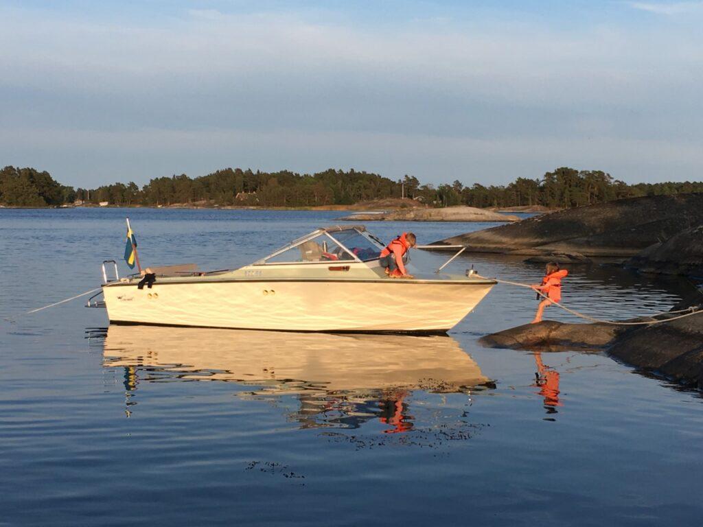 Två barn lägger an en motorbåt.