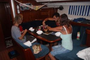 Tre personer sitter runt ett bord på en båt och äter.