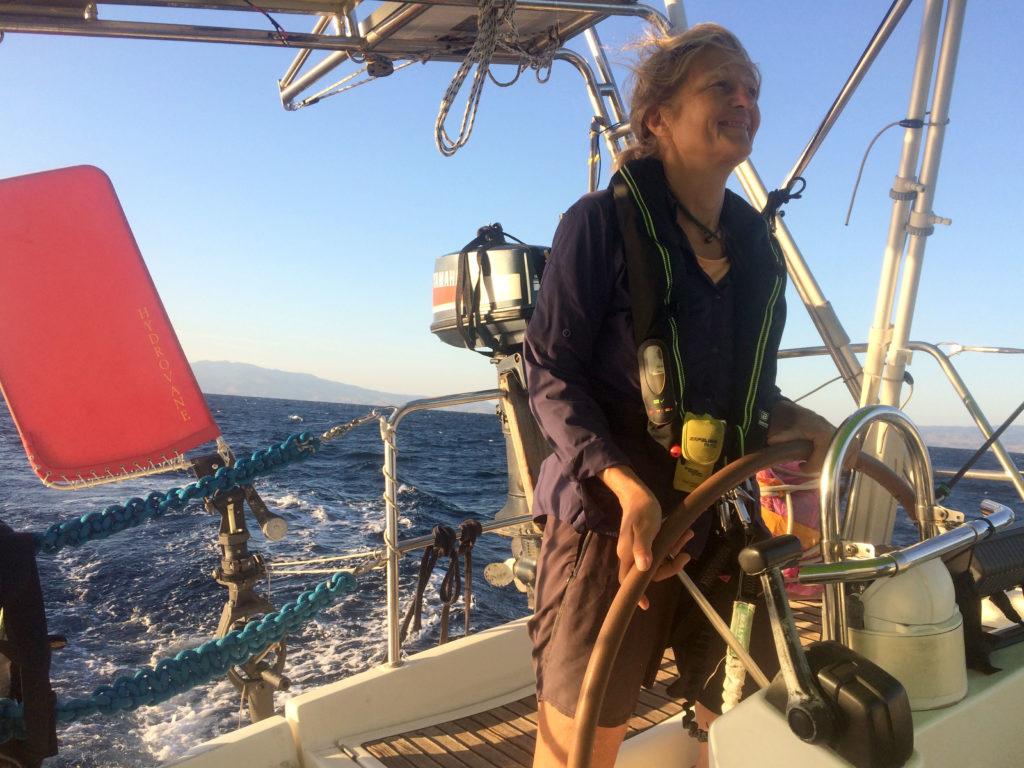 En kvinna styr en segelbåt och ler.