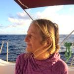 En kvinna med blont hår sitter på en båt och tittar ut mot horisonten.