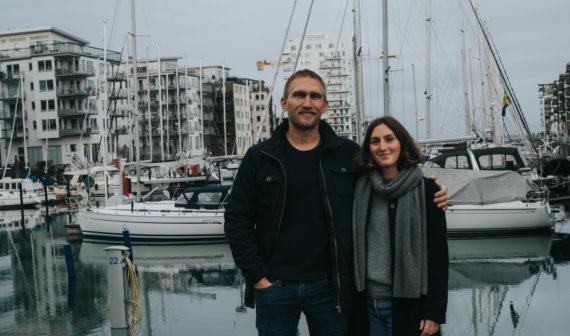 Ett par står framför en hamn och ler.