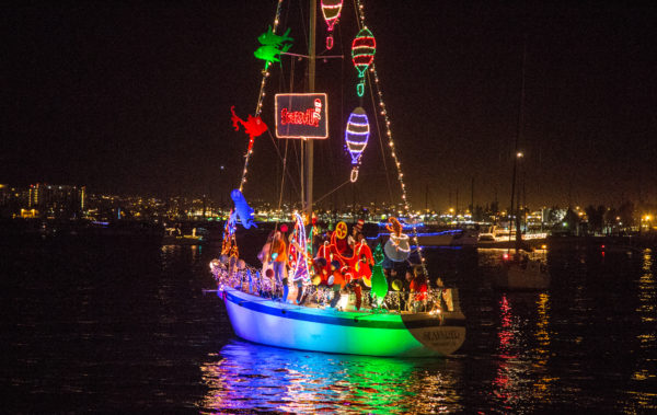 En segelbåt går för motor på natten och är helt belamrad av julbelysning.