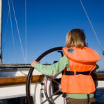Little girl sailing with her life jacket on
