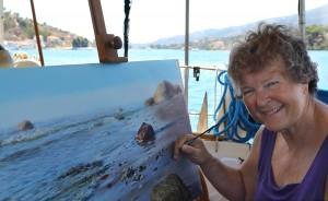 Elizabeth målar på svaj vid Poros